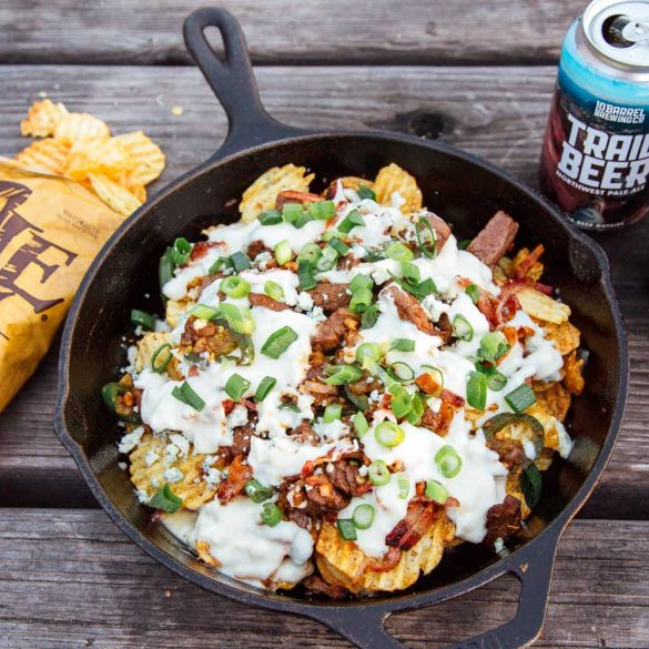 Nachos with steak and beer-cheese sauce in a cast iron skillet. Bag of kettle chips and can of beer in frame.