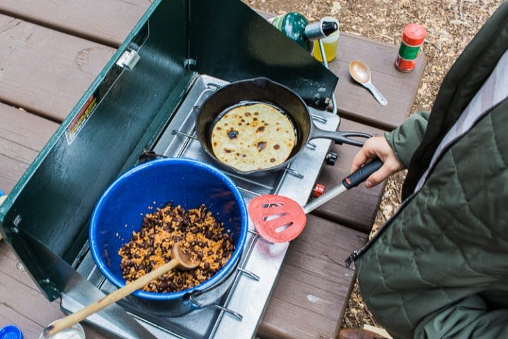 Megan cooking vegan taco filling over a camp stove