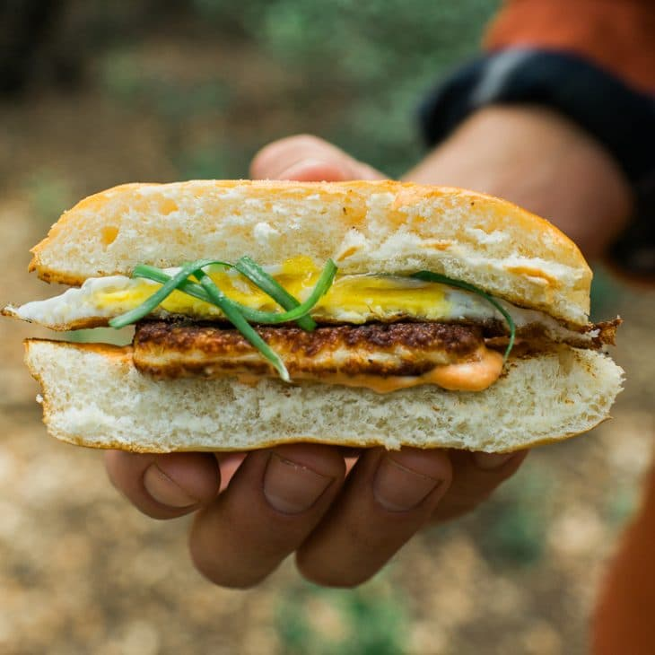 A person holding half an egg and halloumi cheese sandwich.