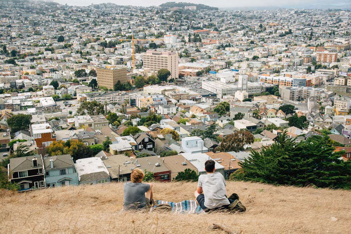 Michael and a friend sitting on Bernal Hill overlooking the city of San Francisco