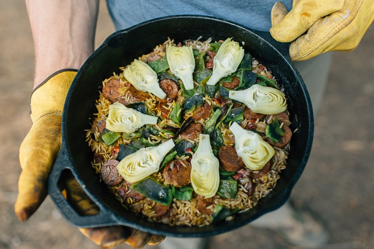 Michael holding a cast iron skillet filled with paella