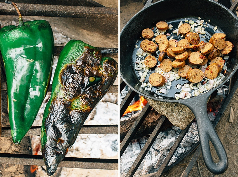 Grilling peppers over a campfire next to a cast iron skillet