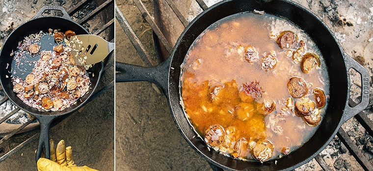 Paella cooking in a cast iron skillet over a campfire
