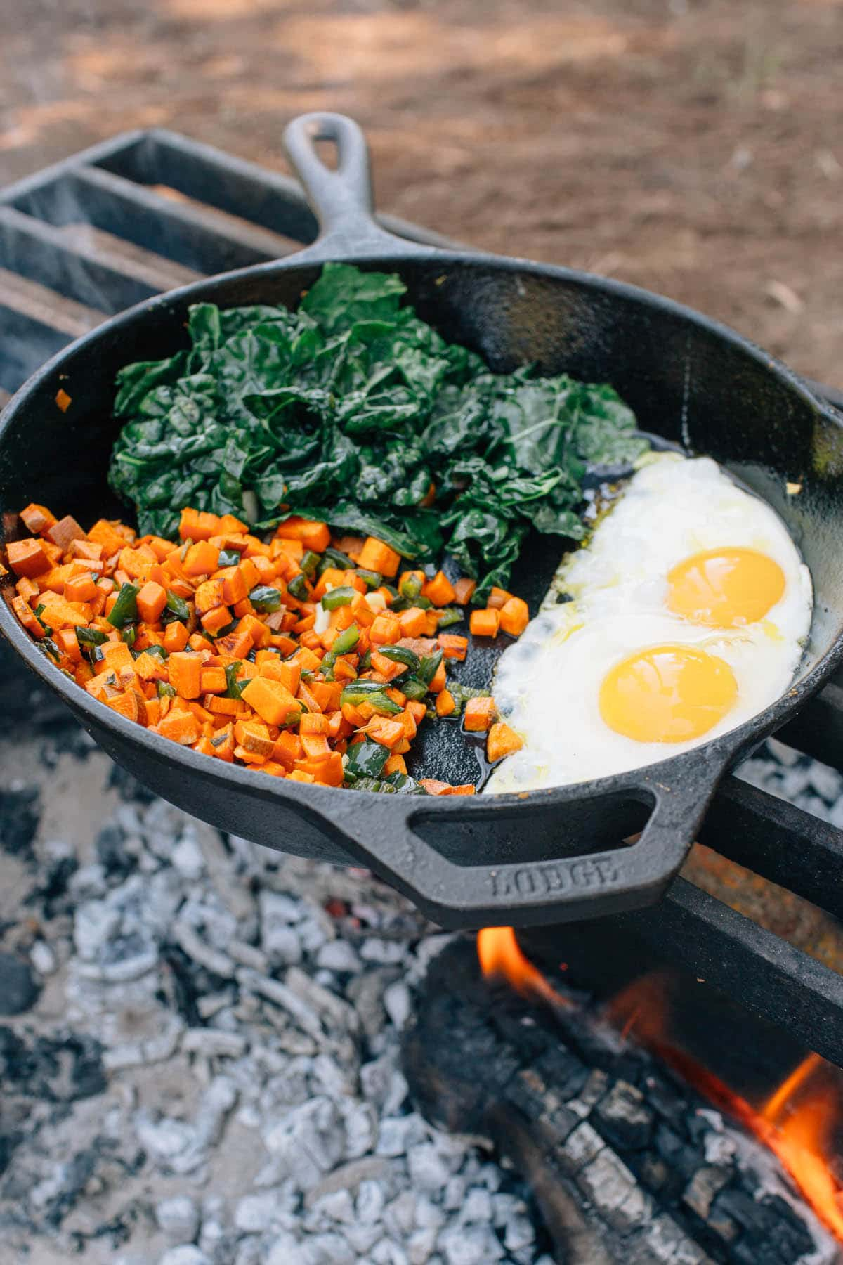 Breakfast hash and eggs in a cast iron skillet over a campfire