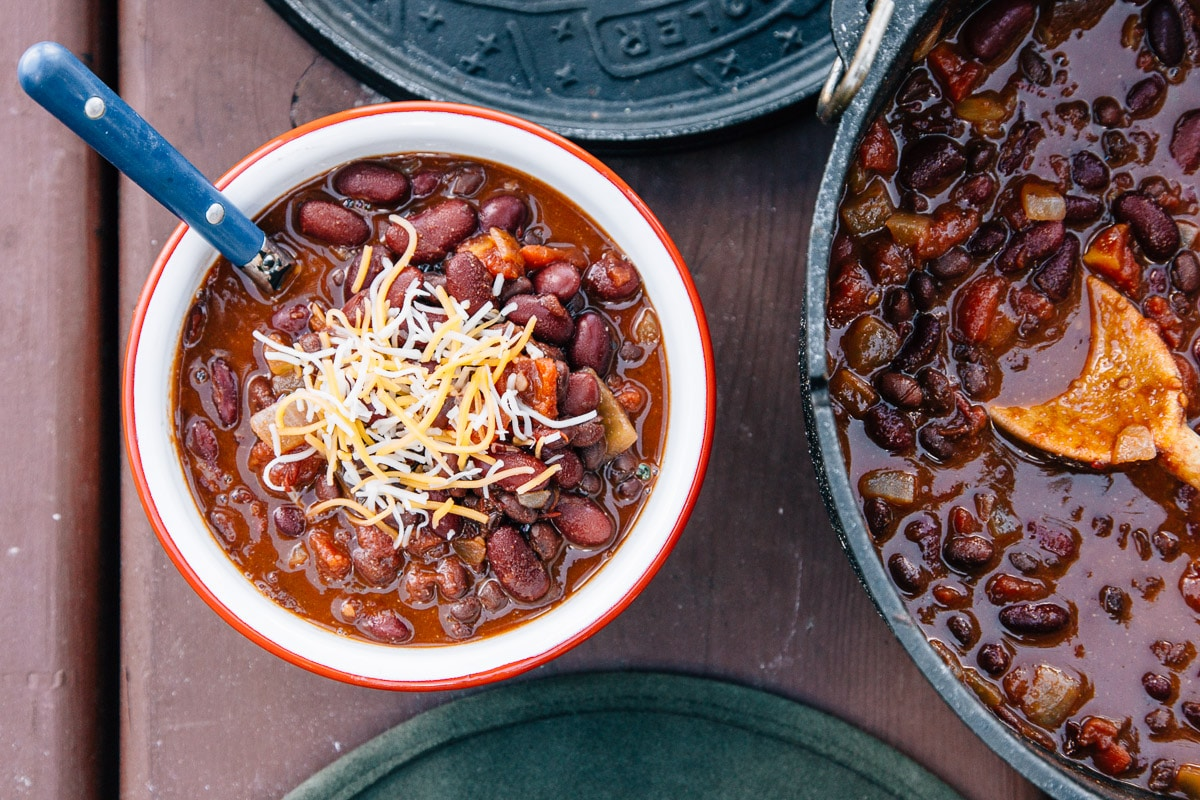 5 can chili in a red and white camping bowl next to a Dutch oven.