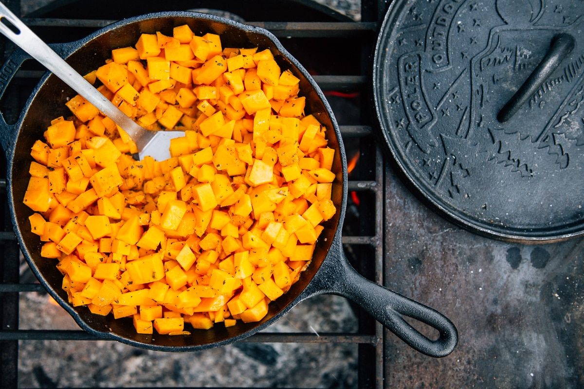 Cast iron skillet full of cubed butternut squash over a campfire