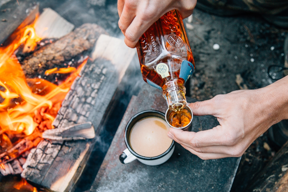 Pouring whiskey into a mug of pumpkin spiced chai with a campfire in the background