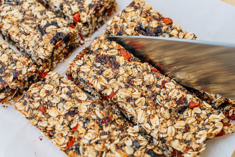 A knife slicing homemade granola bars into bars