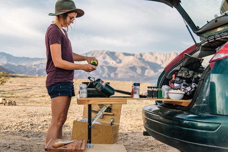 Megan cooking at a camp stove that is on the tailgate of a car