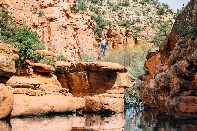 Michael jumping off of a rock into a swimming hole