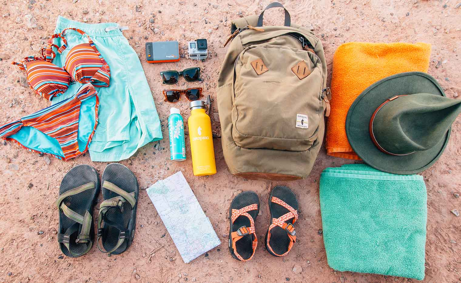 Gear for a swimming hole hike laid out on the ground