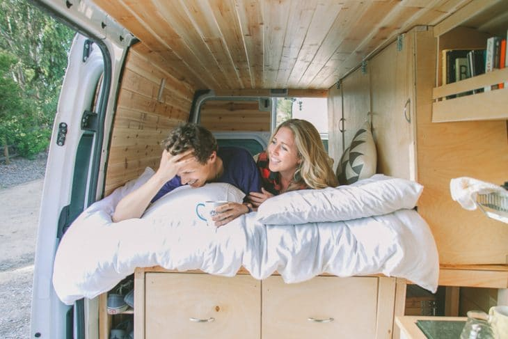 A man and a woman on the bed of their camper van