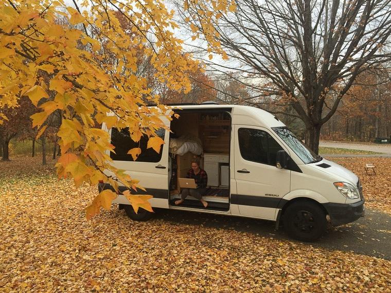A woman sitting in a sprinter camper van