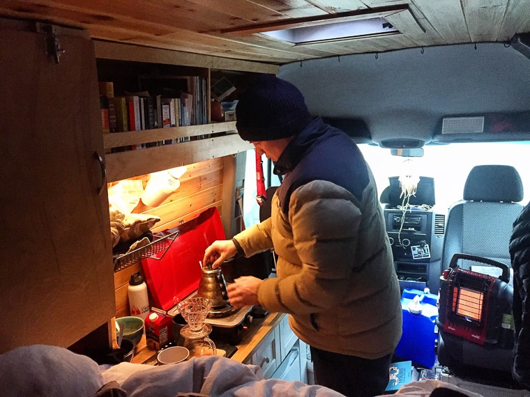 A man making coffee at a stove inside of a camper van