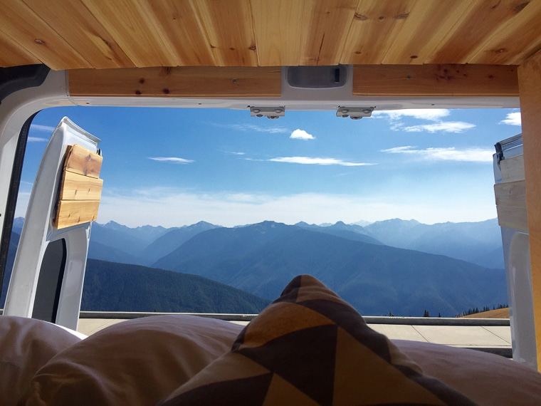 A view of the mountains as seen through the back doors of a camper van