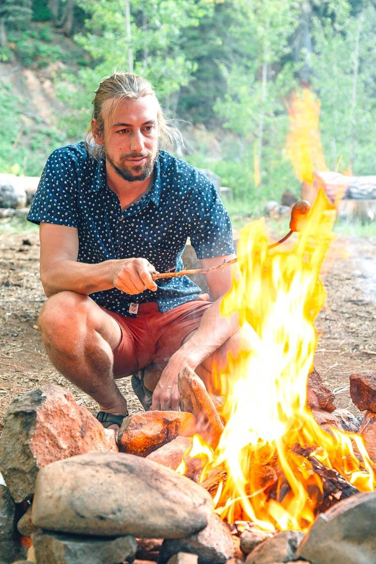 Michael crouched next to a campfire roasting a hotdog on a stick