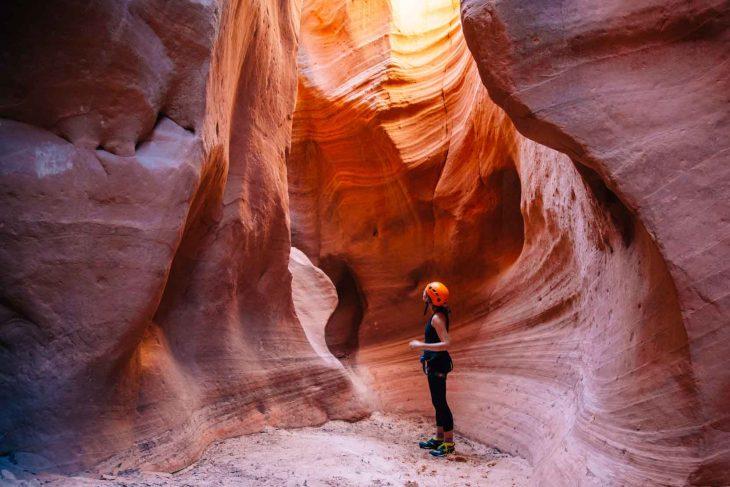 Megan looking up at the walls of a pink and orange slot canyon