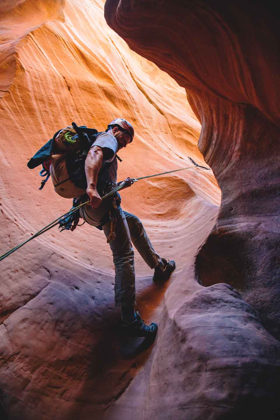A man repelling into a slot canyon