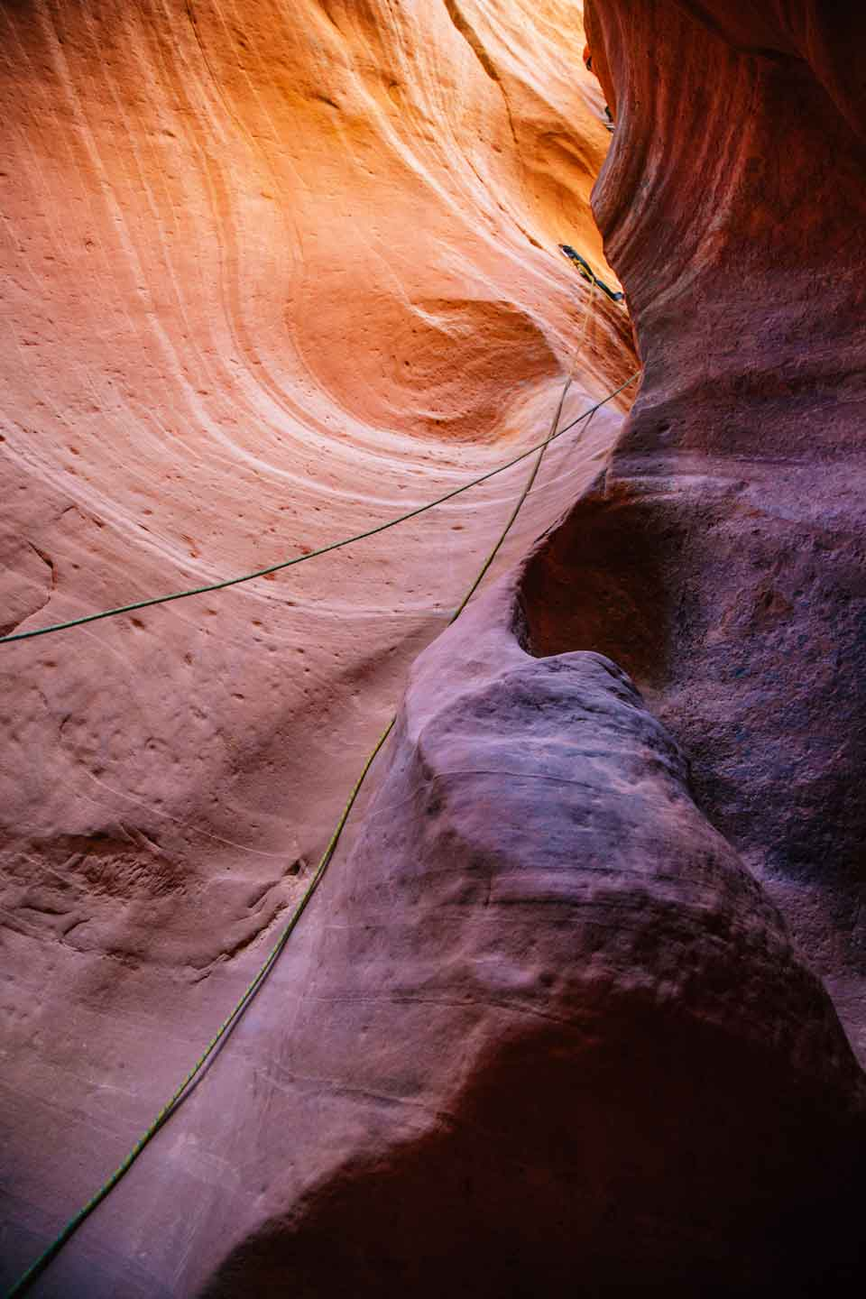 A pink and orange slot canyon with climbing ropes hanging down the walls