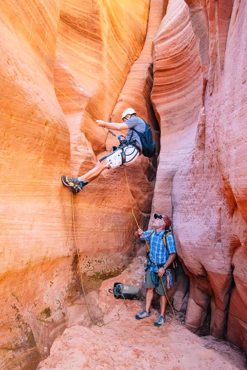 Two men with canyoneering gear in an orange and pink slot canyon