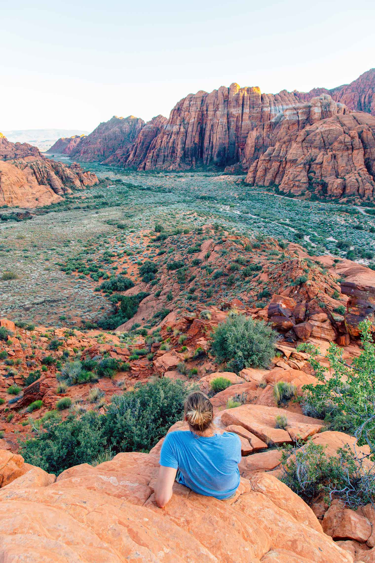 Michael relaxing on a tall rock outcropping overlooking snow canyon state park