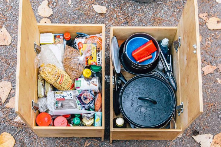 Two wooden crates filled with camping pantry ingredients and camp cooking equipment