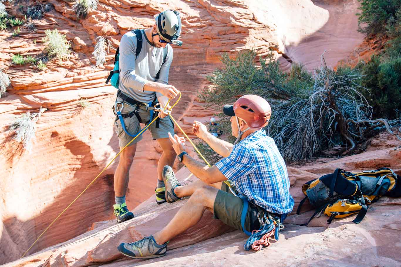 A guide showing Michael how to use ropes to repel into a slot canyon