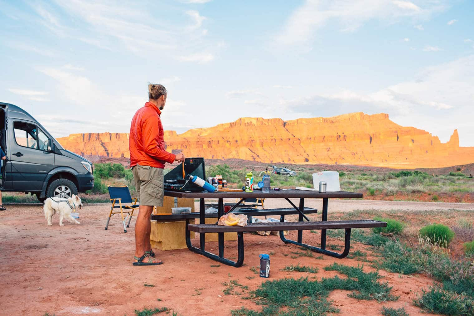Michael cooking on a camping stove with red rocks in the background