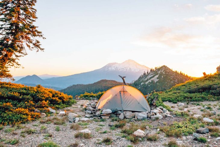 A backpacking tent set up with Mount Shasta in the distance