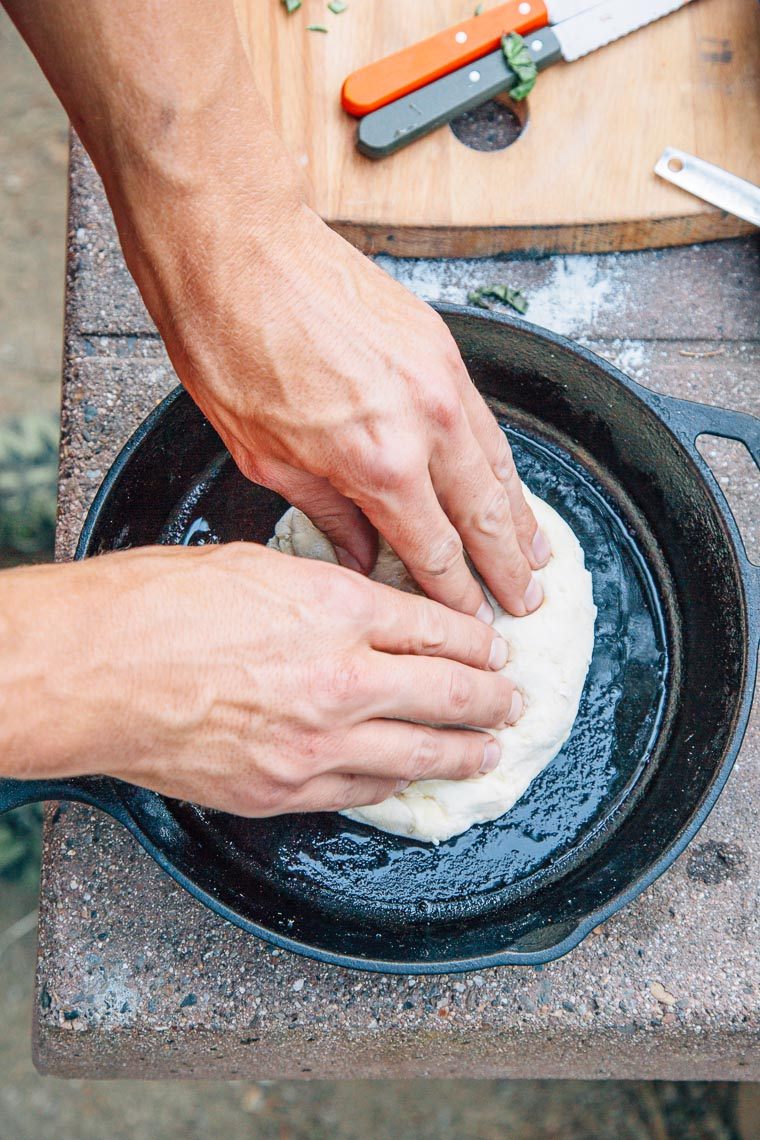 Michael stretching out pizza dough into a cast iron skillet