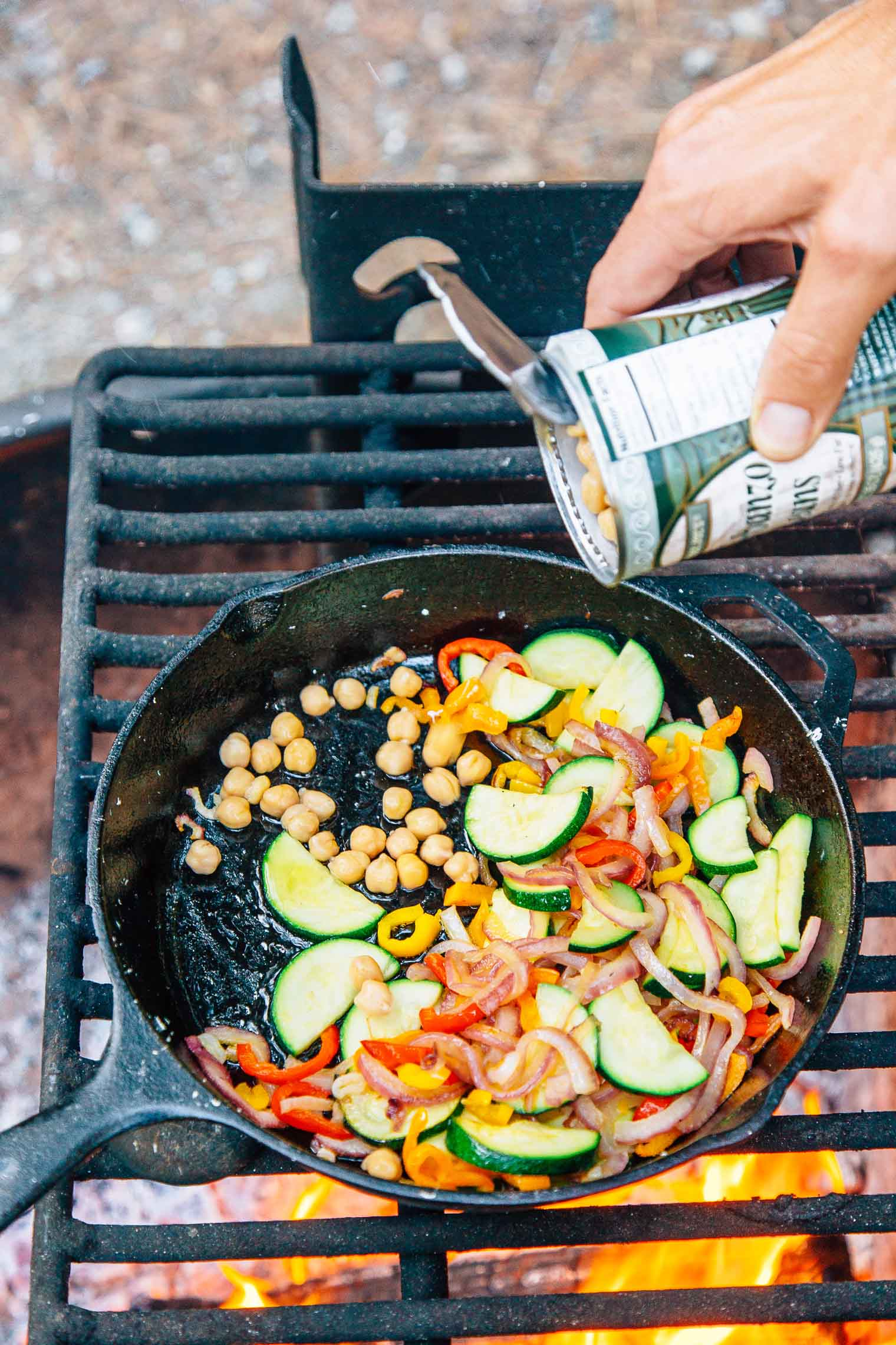 Michael adding chickpeas to a cast-iron skillet full of vegetables