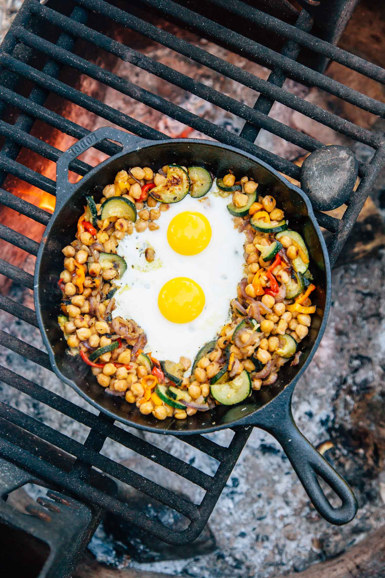 Chickpea and vegetable hash with two eggs in a cast iron skillet over a campfire
