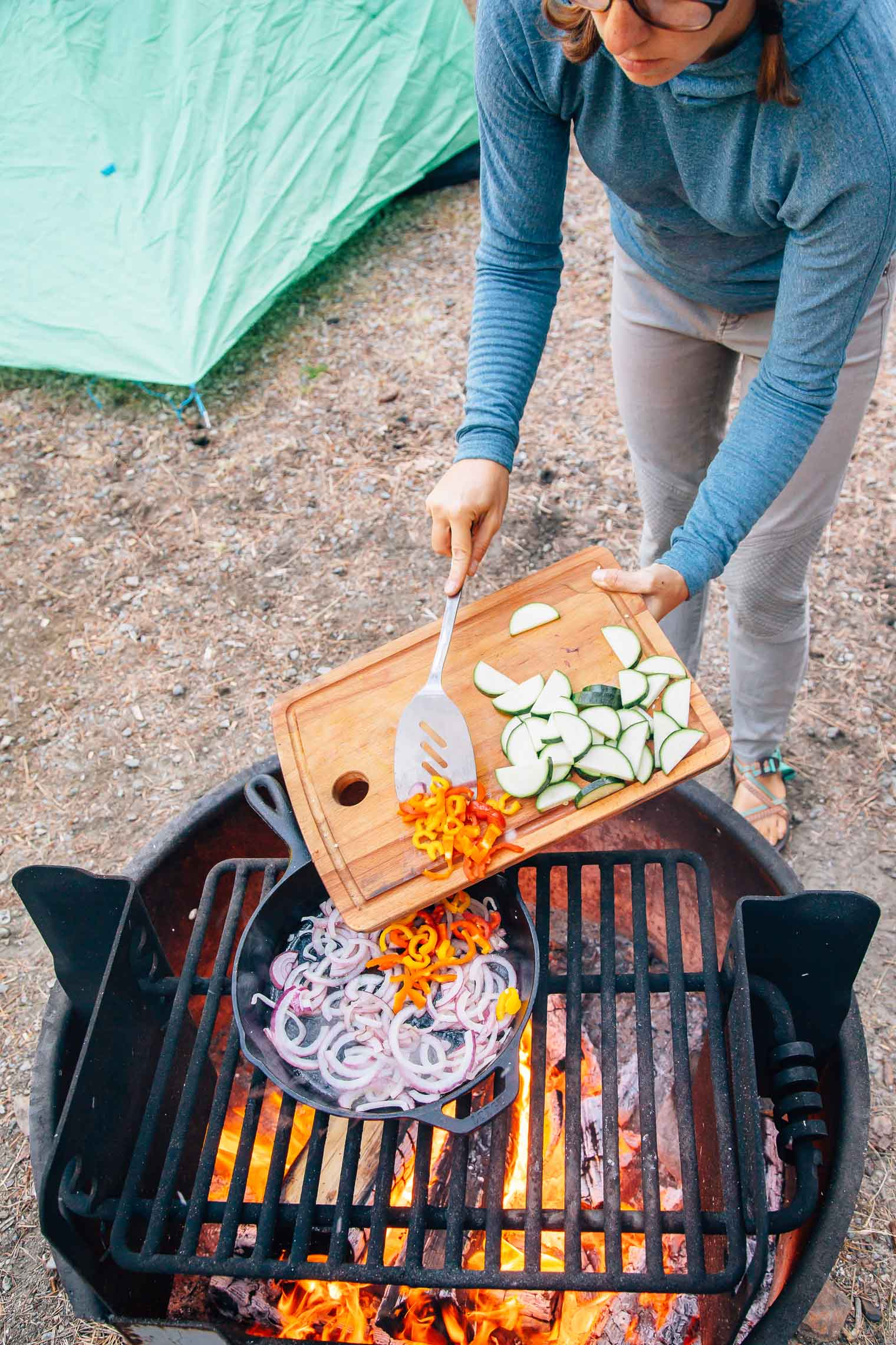 Megan is transferring chopped vegetables from a cutting board into a cast-iron skillet that's on a campfire