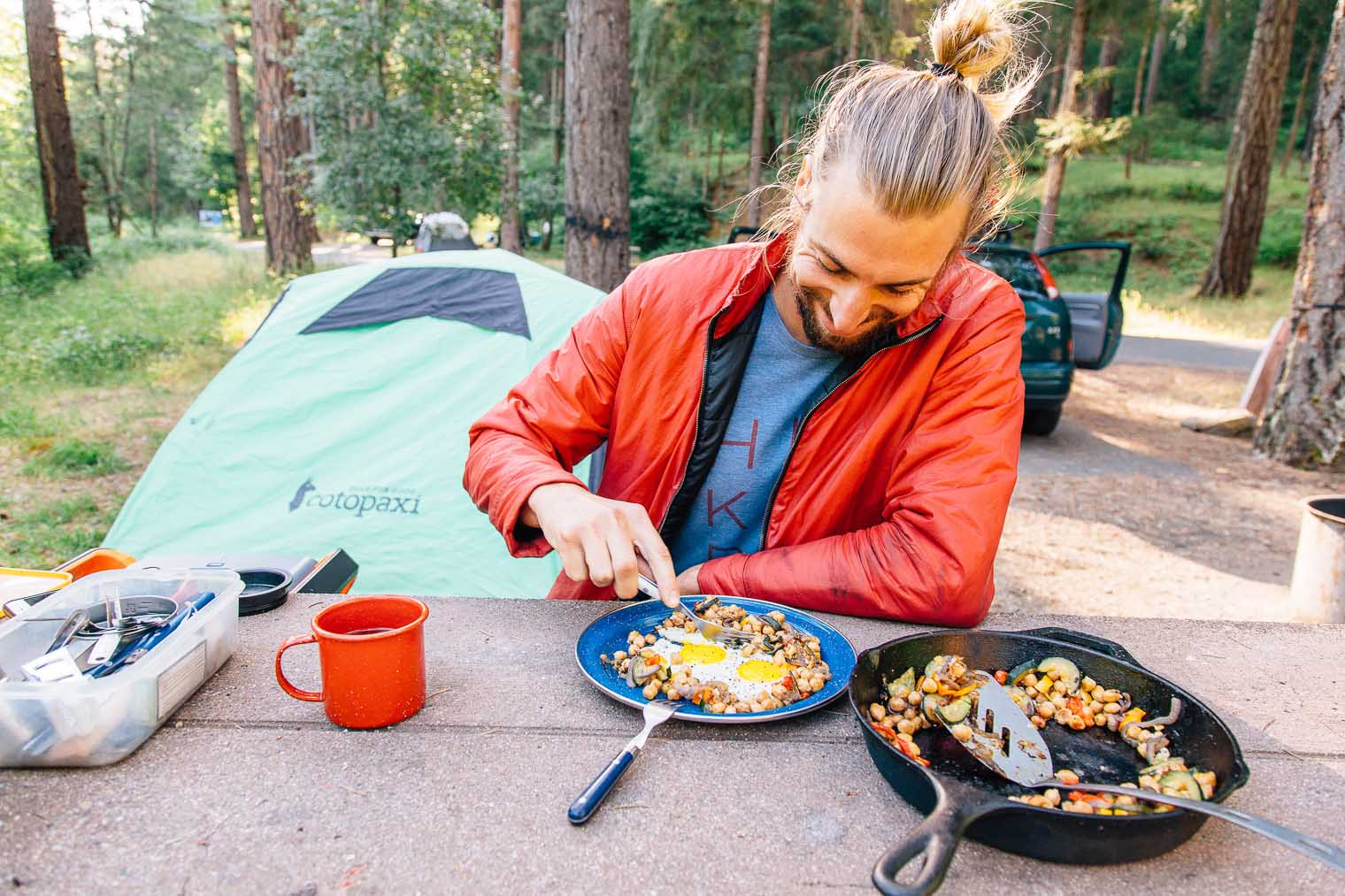 Michael sitting at a camp table eating a plate of chickpea hash with a tent in the background