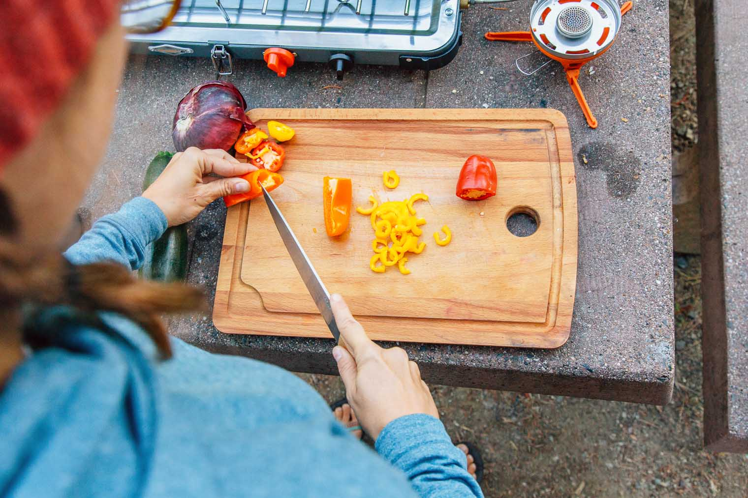 Megan chopping bell peppers on a wooden cutting board