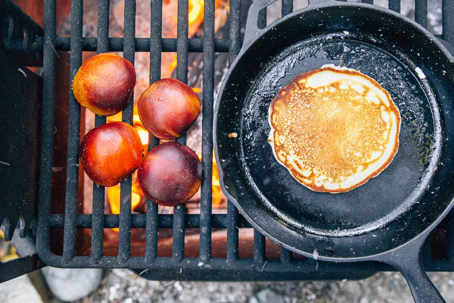 Pancakes in a skillet and halved peaches on a campfire grate