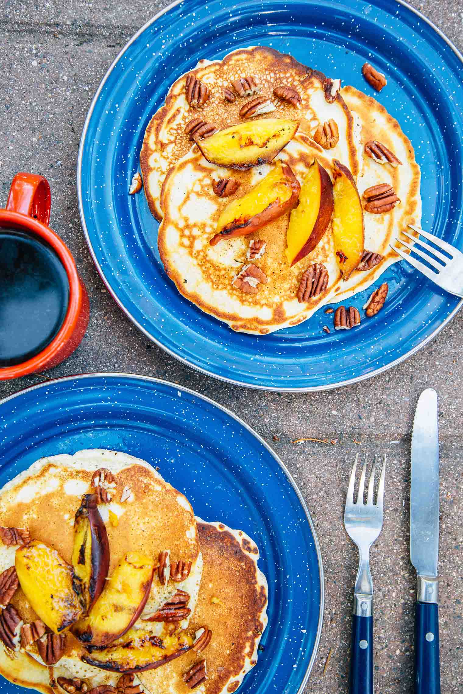 Grilled peach and pecan pancakes stacked on a blue camping plate.