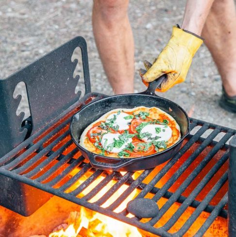 Michael picking up a cast iron skillet filled with pizza off of a campfire grill