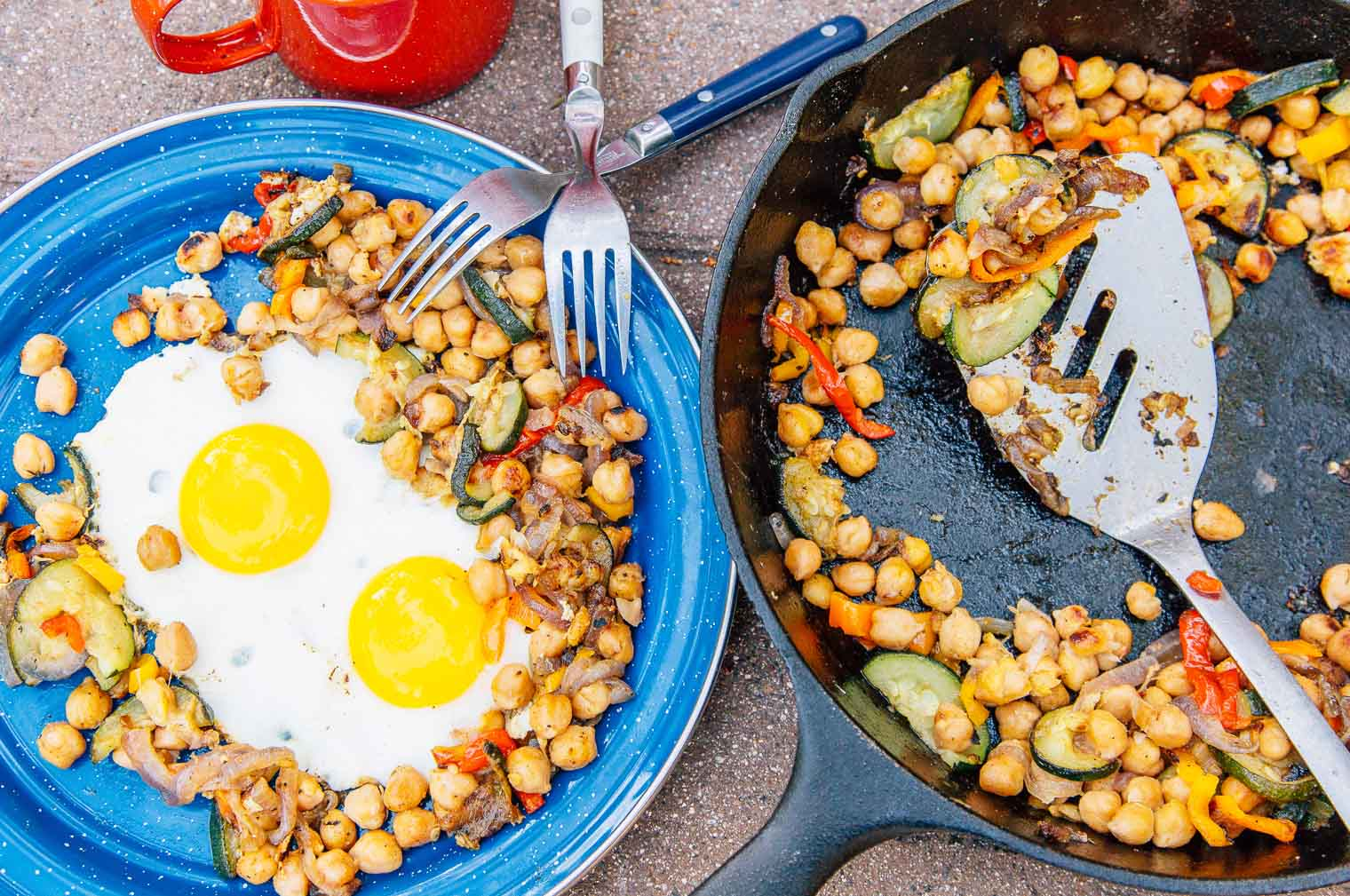 Cast iron skillet with chickpeas next to a blue camping plate with fried eggs
