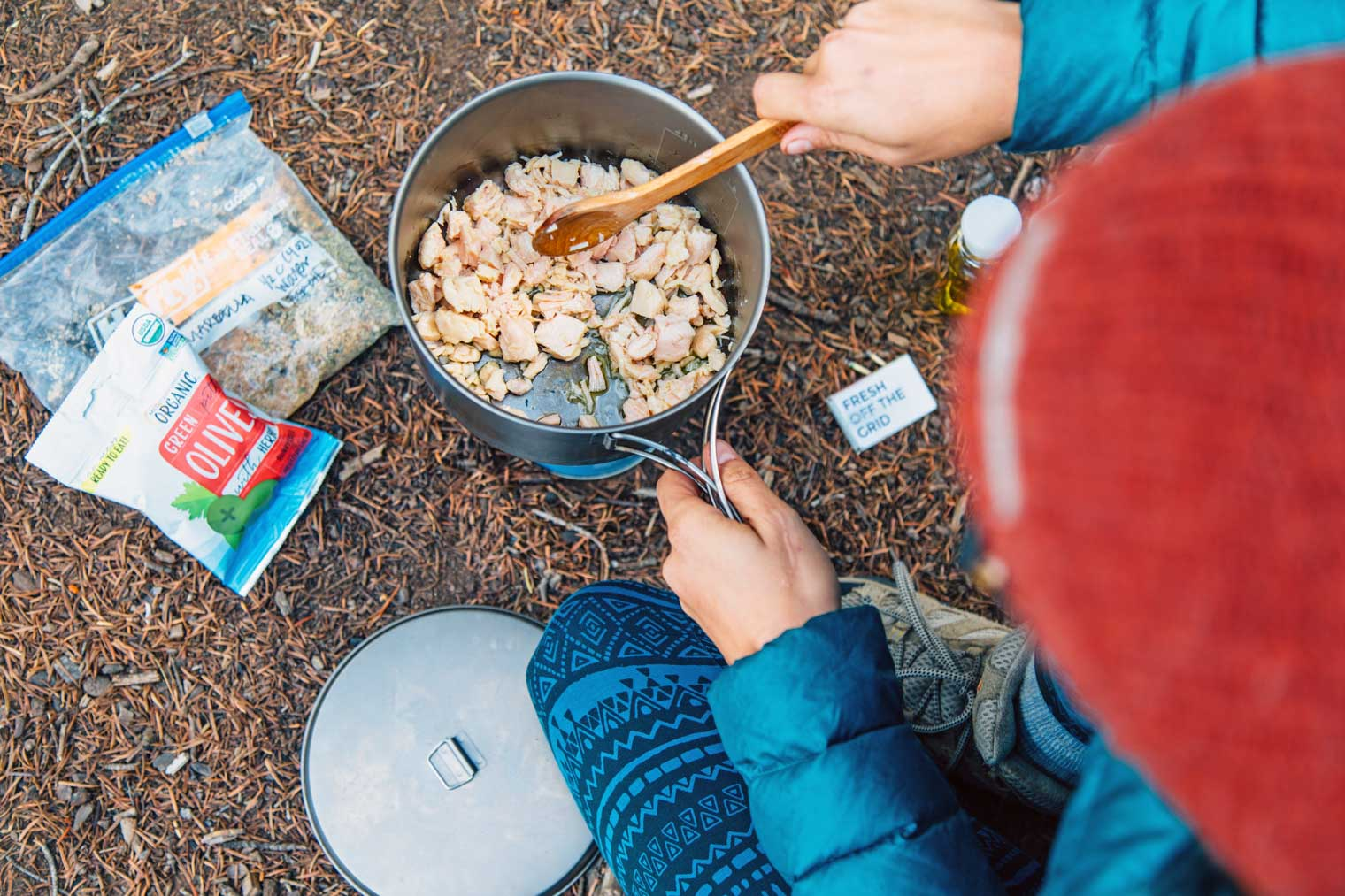 Megan heating pieces of chicken in a backpacking pot