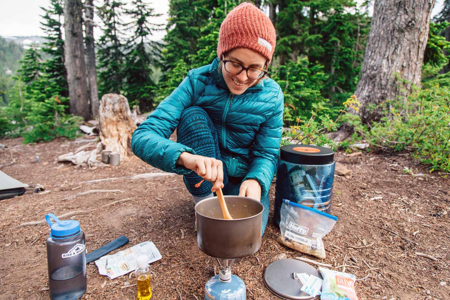 Megan stirring the contents of a pot that is on a backpacking stove