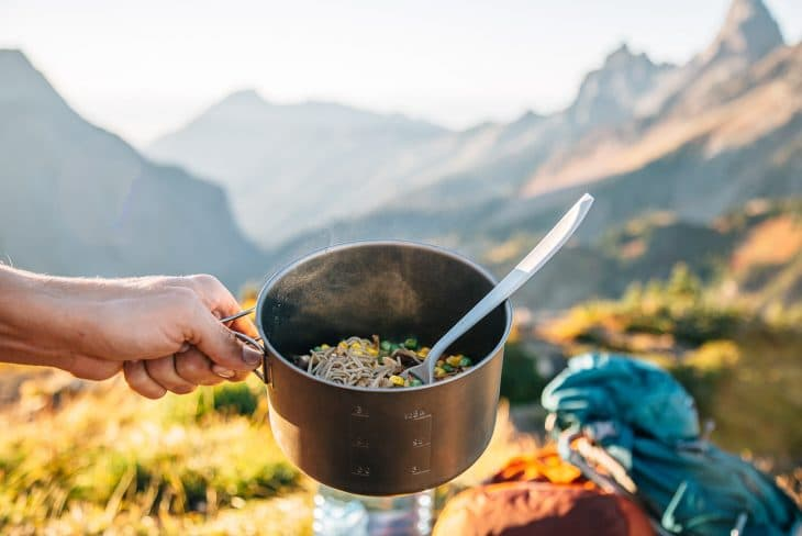 Michael holding a backpacking pot filled with ramen with mountains in the distance