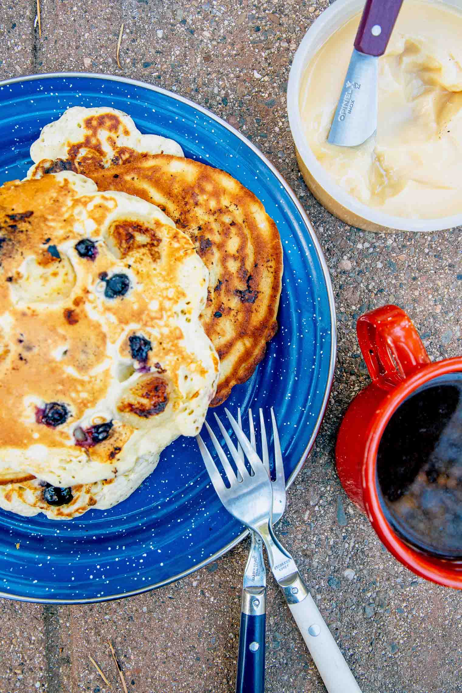 A stack of blueberry banana pancakes on a plate next to a cup of coffee