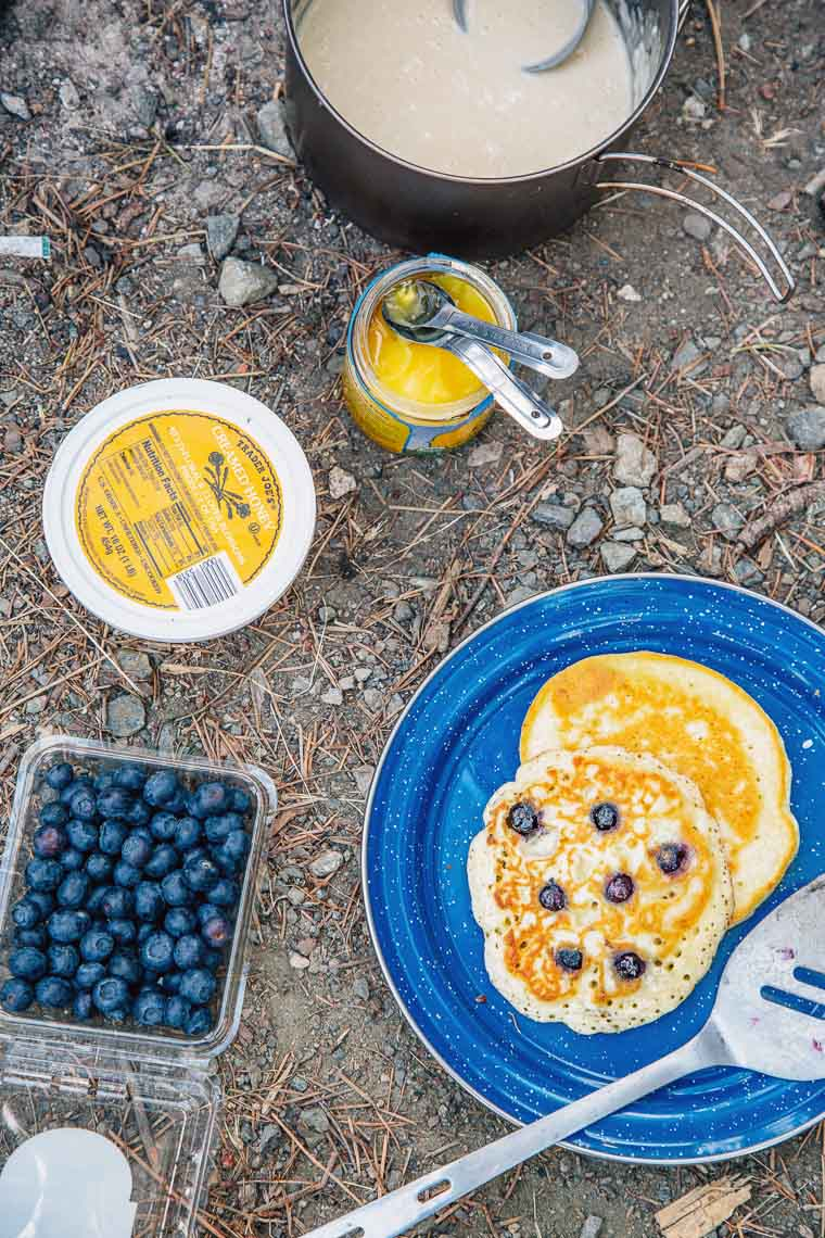 A stack of blueberry pancakes on a plate next to a container of blueberries