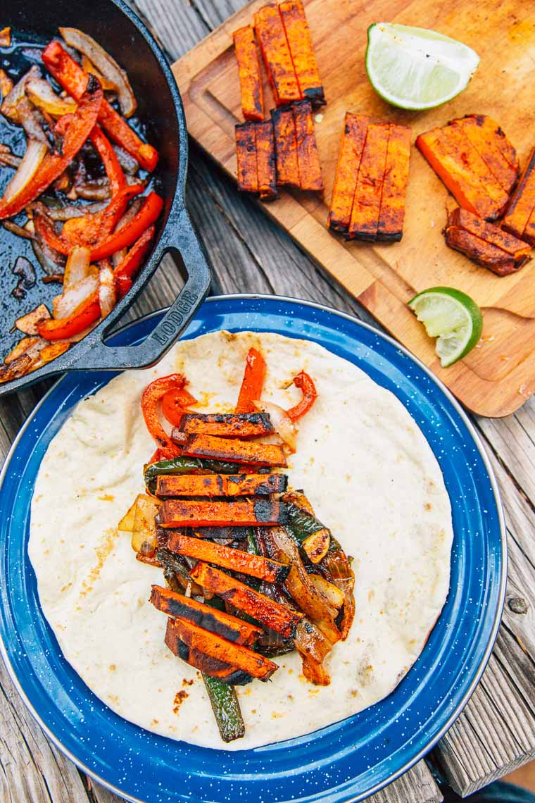 "Grilled sweet potato ""steaks"", roasted peppers and onions, and a New Mexican chile marinade, these vegan campfire fajitas are new take on on an old classic."