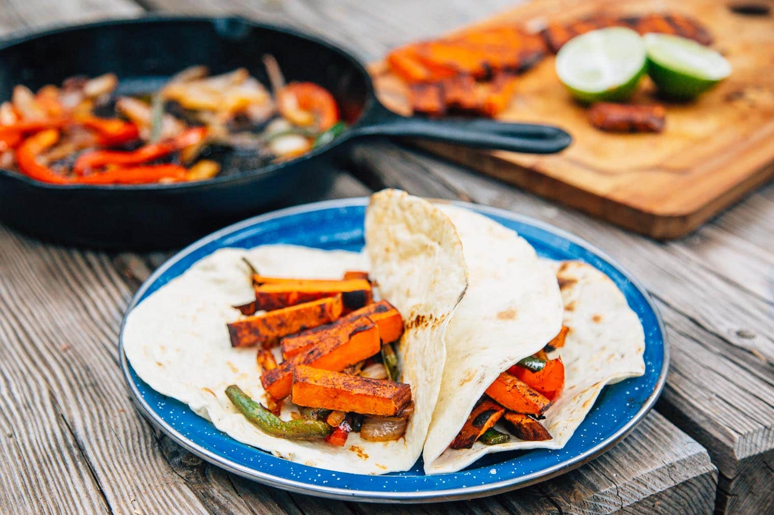 Fajitas filled with sweet potatoes, roasted peppers and onions on a blue plate