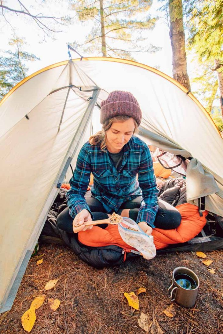 Megan sitting at the entrance of a backpacking tent eating granola out of a baggie