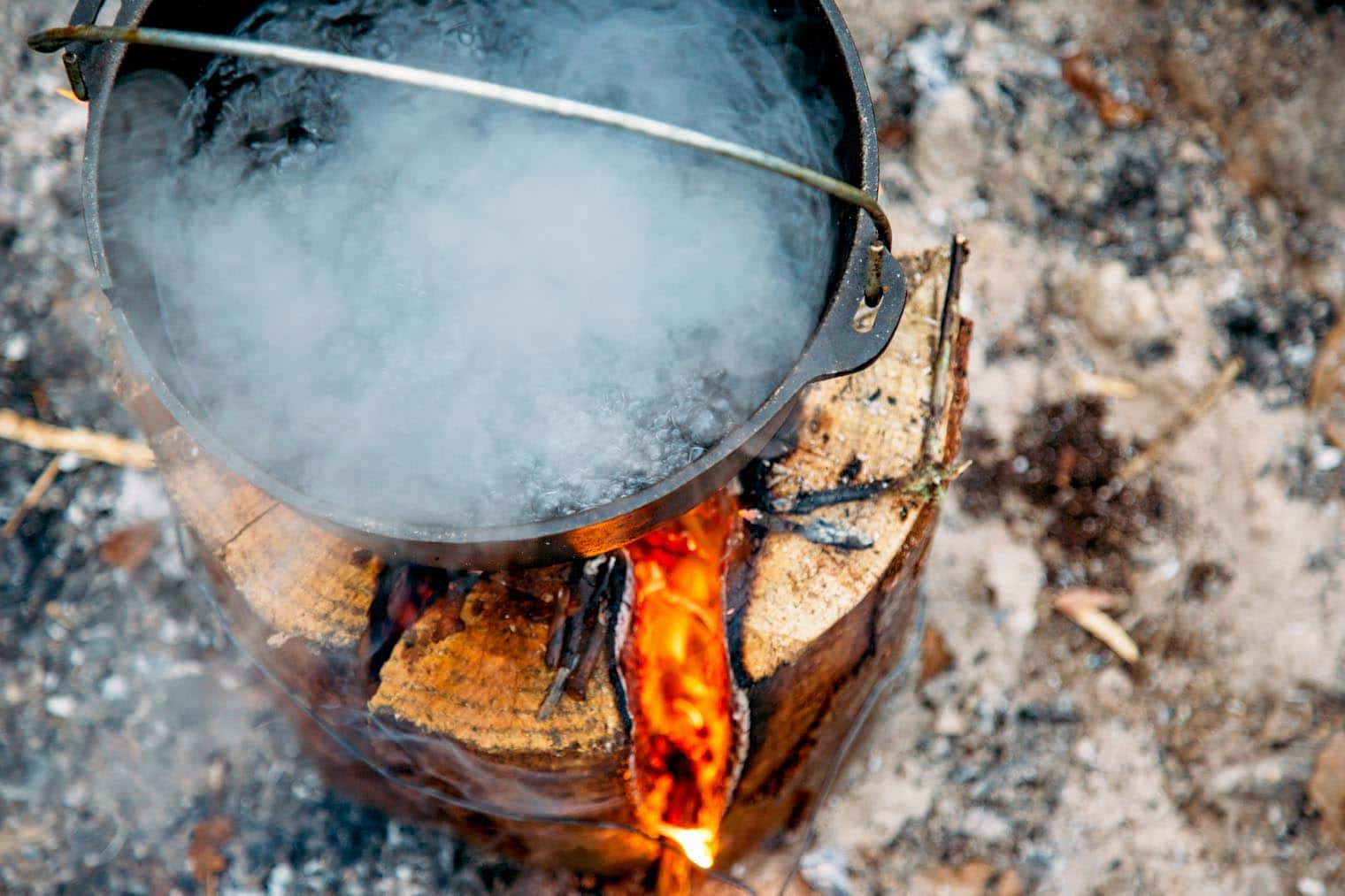 A Dutch oven with boiling water on top of a Swedish firelog