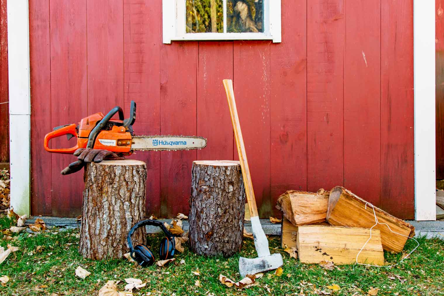 Firewood and wood cutting tools in front of a red shed