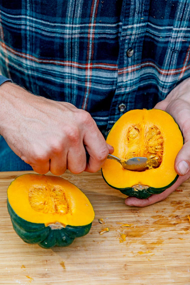 Michael scooping seeds out of half an acorn squash